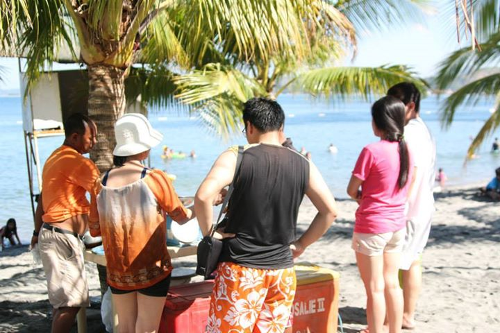 The tourists (busy buying some squid for snack)